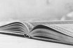 Czarny i biały fotografia otwarta książka na stole, selekcyjnej ostrości i płyciznie, obraz stock