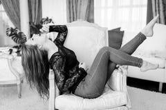 Czarny i biały fotografia podniecająca piękna młoda dama relaksuje w krześle Zdjęcia Royalty Free