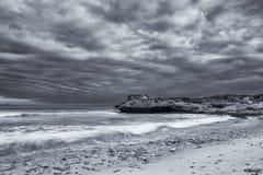 Czarny i biały krajobraz ocean kołysa artystycznego przeciw i chmurnieje Obrazy Stock