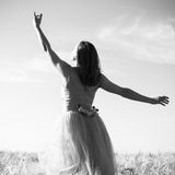 Czarny i biały romantyczna piękna młoda dama ma zabawy pozycję w polu z ręką do nieba na outdoors tle Obraz Stock