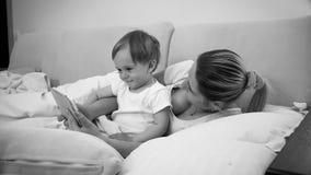 Czarny i biały wizerunek matka z jej dziecko syna lying on the beach w łóżku z cyfrową pastylką Obraz Royalty Free
