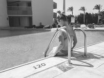 Czarny i biały wizerunek piękna młoda kobieta w bikini obsiadaniu na basen stronie Dziewczyna relaksuje i ma zdjęcie stock