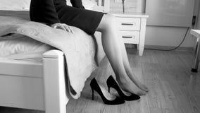 Czarny i biały zbliżenie wizerunek młodej kobiety obsiadanie na łóżku i brać daleko szpilki buty obrazy stock