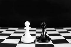Czarny i biały szachowi pionkowie Bitwa równi rywale Zdjęcie Stock