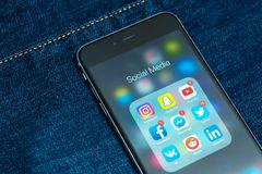 Czarny Jabłczany iPhone z ikonami ogólnospołeczny medialny zastosowanie na ekranie z drelichowym cajgu tłem obrazy stock