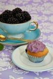 Czarny jagodowe babeczki z filiżanką owoc Fotografia Royalty Free