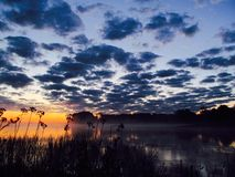czarny jezioro przy zmierzchem Obrazy Stock