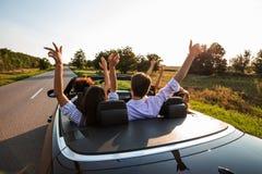 Czarny kabriolet jest na wiejskiej drodze Firma młode dziewczyny i faceci siedzimy w samochodowym chwycie ich ręki na w górę a fotografia stock