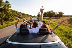 Czarny kabriolet jest na wiejskiej drodze Firma młode dziewczyny i faceci siedzimy w samochodowym chwycie ich ręki na w górę a zdjęcia royalty free