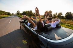 Czarny kabriolet jest na wiejskiej drodze Firma młode dziewczyny i faceci siedzimy w samochodowym chwycie ich ręki na w górę a zdjęcie stock