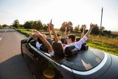 Czarny kabriolet jest na wiejskiej drodze Szczęśliwa grupa młode dziewczyny i faceci siedzimy w samochodowym chwycie ich ręki w g obraz royalty free