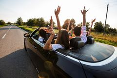 Czarny kabriolet jest na wiejskiej drodze Szczęśliwa grupa młode dziewczyny i faceci siedzimy w samochodowym chwycie ich ręki w g obraz stock