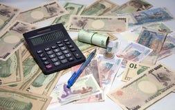 Czarny kalkulator i błękitny ballpoint pióro z rolka Tajlandzkimi banknotami używamy gumowego zespołu na różnorodnych narodów ban Fotografia Royalty Free