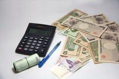 Czarny kalkulator i błękitny ballpoint pióro z rolka Tajlandzkimi banknotami używamy gumowego zespołu i różnorodnych narodów bank Zdjęcie Royalty Free