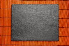 Czarny kamienia talerz na czerwonym bomboo maty tle z copyspace zdjęcie stock
