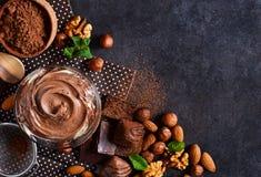 Czarny karmowy tło z kakao, dokrętkami i czekoladową pastą, wierzchołek zdjęcia royalty free