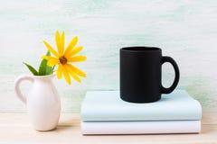 Czarny kawowego kubka mockup z żółtym rosinweed kwitnie w miotaczu Zdjęcia Royalty Free