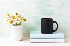 Czarny kawowego kubka mockup z białym śródpolnego chamomile bukietem w brzęczeniach Zdjęcie Royalty Free