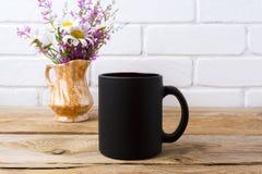 Czarny kawowego kubka mockup z chamomile i purpurami kwitnie w golu Fotografia Stock