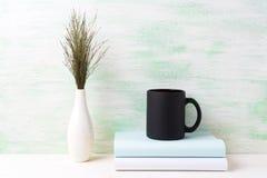 Czarny kawowego kubka mockup z ciemną łąkową trawą w wazie i książkach Fotografia Royalty Free