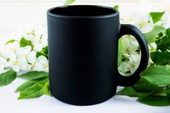 Czarny kawowego kubka mockup z jabłczanym okwitnięciem Zdjęcia Stock