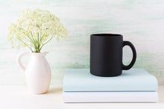 Czarny kawowego kubka mockup z książkami i czułymi białymi kwiatami Obrazy Royalty Free
