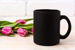 Czarny kawowego kubka mockup z magenta menchii tulipanów bukietem Obrazy Royalty Free
