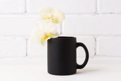 Czarny kawowego kubka mockup z miękką żółtą orchideą Obrazy Royalty Free