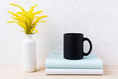Czarny kawowego kubka mockup z ornamentacyjną złotą trawą i książkami Fotografia Stock