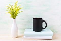 Czarny kawowego kubka mockup z ornamentacyjną zieloną trawą i książkami Zdjęcie Stock