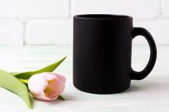 Czarny kawowego kubka mockup z różowym tulipanem Fotografia Royalty Free