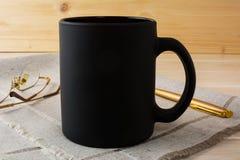Czarny kawowego kubka mockup z szkłami i piórem Fotografia Royalty Free
