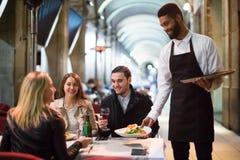 Czarny kelner porci stół na tarasie Zdjęcia Stock