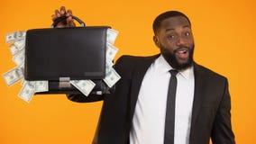 Czarny kierownik w kostiumu pokazuje teczkę dolary pełno, bankowości usługa, kredyt zbiory