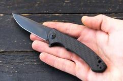 Czarny kieszeniowy nóż w ręce Nóż w prawej ręce Zdjęcie Royalty Free