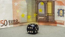 Czarny kostka do gry grzebak jest szarości powierzchni tła pięćdziesiąt euro banknotem Fotografia Royalty Free