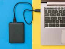 Czarny laptop na tle, dysk twardy i Mieszkanie nieatutowy Poj?cie pomocniczy magazyn zdjęcia royalty free