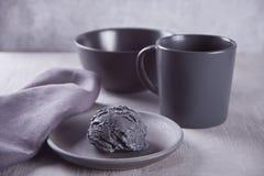 Czarny lody na czarnym ceramicznym talerzu z szarą pieluchą na szarym stole zdjęcia stock