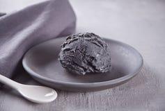 Czarny lody na czarnym ceramicznym talerzu z szar? pieluch? na szarym stole obraz royalty free