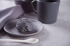 Czarny lody na czarnym ceramicznym talerzu z szar? pieluch? na szarym stole obrazy royalty free
