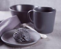Czarny lody na czarnym ceramicznym talerzu z szar? pieluch? na szarym stole obraz stock