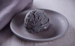 Czarny lody na czarnym ceramicznym talerzu z szar? pieluch? na szarym stole fotografia royalty free