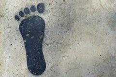 Czarny ludzki odcisk stopy na cementowej podłoga Zdjęcie Royalty Free