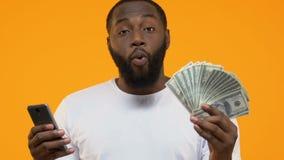 Czarny męski używa smartphone zastosowanie pokazuje dolarowych rachunki, spienięża z powrotem usługi zdjęcie wideo