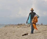 Czarny męski chusteczka handlarz oferuje jego towary na piaskowatym Zdjęcia Royalty Free