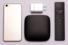 Czarny multimedii TV pudełko, daleki kontroler, mądrze telefon i ładowarka, Zdjęcia Royalty Free