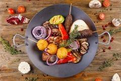 Czarny naczynie z grilla mięsem Życie na drewnianym tle zdjęcie stock