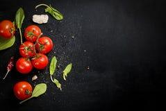 Czarny nieociosany tabletop z gałąź pomidory i ziele, wierzchołek rywalizuje Zdjęcia Royalty Free
