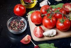 Czarny nieociosany tabletop z gałąź pomidory i ziele, wierzchołek rywalizuje Obraz Stock