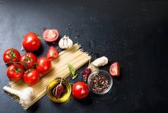 Czarny nieociosany tabletop z gałąź pomidory i ziele, wierzchołek rywalizuje Obrazy Royalty Free